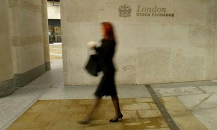 A woman walks past the London Stock Exchange