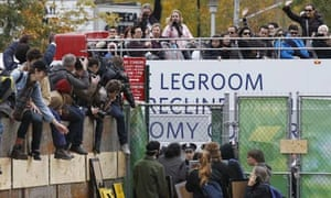 Tourists watch protesters as they climb into a vacant lot next to Duarte Square in New York