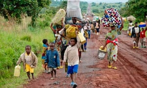 People walk along the main road to Goma after fleeing fighting in Kibumba