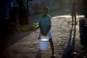 24 hours in pictures: A boy carries a bucketful of water in Port-au-Prince, Haiti