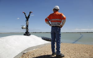 From the agencies: A worker stands at the edge of an untreated water at a QGC reverse