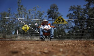 From the agencies: Farmer sits in front of an access gate owned by coal seam gas miner Santos