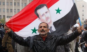 A pro-Assad demonstrator holds a Syrian flag bearing the portrait of his president