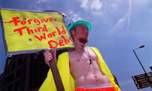 A protester in the City of London holds a placard advocating the abolition of Third World Debt.
