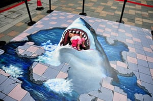 3D pavement art: 17 July 2011: A child plays on a 3D street painting in Fuzhou, China