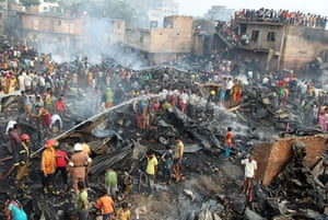 24 hours in pictures: Dhaka, Bangladesh: Firefighters spray water after a fire at a slum