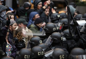 24 hours in pictures: Portland, US: A police officer uses pepper spray