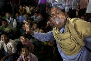 24 hours in pictures: Sonepur, India: A man eats a lit cigarette