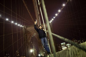 Occupy, Day of Action: An Occupy protestor raises his fist in the air while on the Brooklyn Bridge