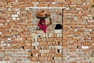 24 hours: A construction labourer carries bricks on her head in Ahmedabad