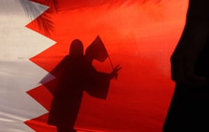 24 hours: A woman carrying a national flag is seen gesturing behind a Bahraini flag
