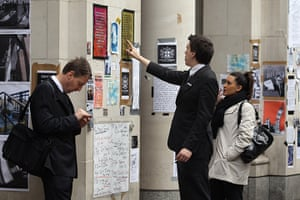 Signs at Occupy London: Passers-by read protest posters on the walls at the Occupy London camp
