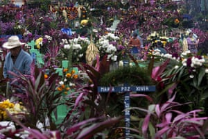 All saints day: Family members decorate the graves of a departed relatives, Guatemala