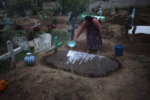 All saints day: A woman pours lime onto a grave in the Cemetery of Sumpango Sacatepequez