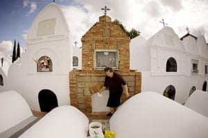 All saints day: A woman clean's the grave of a relative in the cemetery , Spain