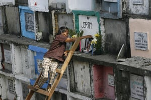 All saints day: A mother uses a ladder to reach her son's tomb in Manila