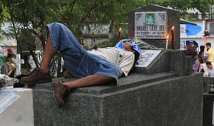 All saints day: A man sleeps atop the tomb of a relative at a cemetery in Manila