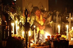 All saints day: A man rests at the grave site during Day of the Dead, Mexico
