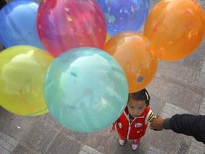 FTA: Navesh Chitrakar: A child with balloons looks up during the Newari New Year parade