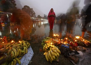 FTA: Navesh Chitrakar: A worshipper waits for sunrise to offer prayers during the Chhat festival