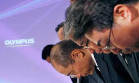 Olympus executives bow after a press conference in Tokyo