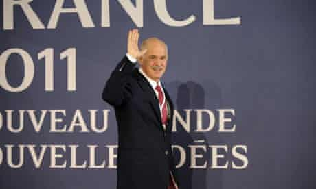 George Papandreou waves as he arrives for a working meeting in Cannes, France, on Wednesday.