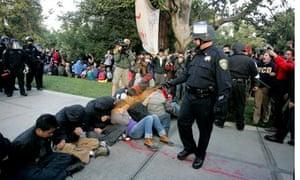 A University of California, Davis, police officer deploys pepper spray on student Occupy protesters