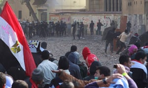Protesters stand opposite riot police near Tahrir Square