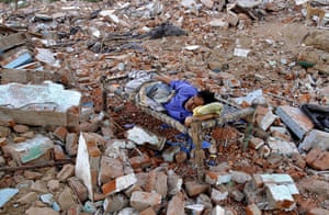 24 hours in pictures: Ahmedabad, India: An Indian man sleeps in the rubble of his demolished hut