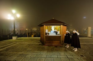 24 hours in pictures: Venice, Italy: Members of a religious order wait to welcome pilgrims