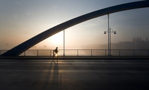 24 hours in pictures: Frankfurt/Oder, Germany: The sun rises behind a pedestrian on a bridge