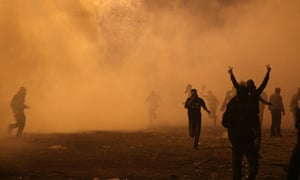 Egyptian protesters flee a barrage of teargas as they clash with riot police near Tahrir Square