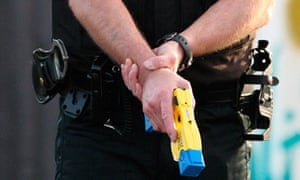 A police officer holds a Taser gun