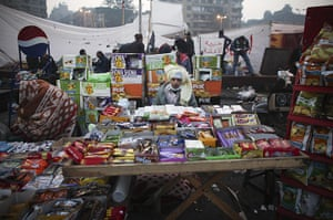 24 hours in pictures: A vendor sits behind his wares in Tahrir Square, Cairo