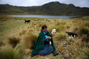 24 hours in pictures: An Andean woman spins wool in front of the Perol lagoon