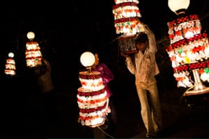24 hours in pictures: ight wallas holds portable chandeliers, New Delhi, India