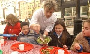 Jamie Oliver serving food to schoolchildren