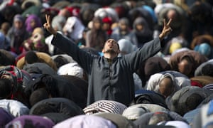 Tahrir Square: A man flashes the V-sign for victory during Friday prayers