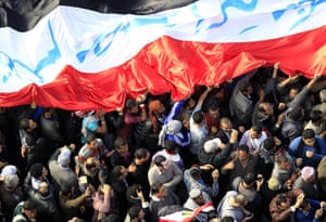 Tahrir Square: Protesters march with a huge flag in Tahrir Square