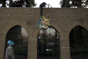 Tehran embassy: A protester removes the emblem of the British embassy in Tehran