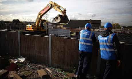 Bailiffs watch a digger clear a plot at Dale Farm