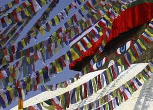 FTA: Navesh Chitrakar : An eye of Lord Buddha is seen behind prayer flags at Boudhanath Stupa