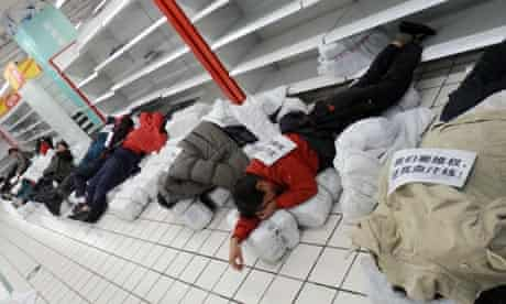 Chinese employees sleep on the ground to protest at a Tesco supermarket, China