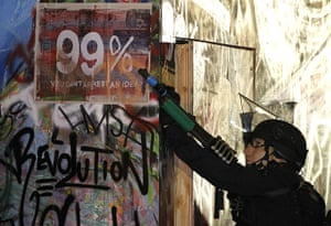 Occupy LA evictions: A Los Angeles police officer points his weapon to demonstrators