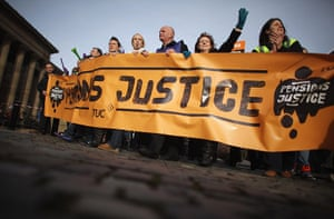 Strikers march: Strikers walk behind a large banner at a march in Liverpool