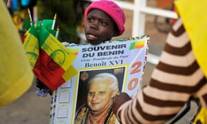 A child sells Pope Benedict souvenir posters