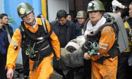 A Chinese coalminer is carried out of the Qianqium mine in Sanmenxia city, Henan province