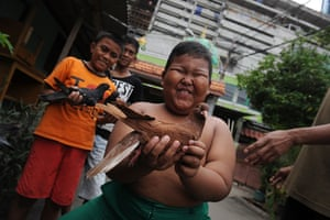 24 hours in pictures: Boys show off their pigeons outside Jami Roudhotul Falah mosque  in JAkarta