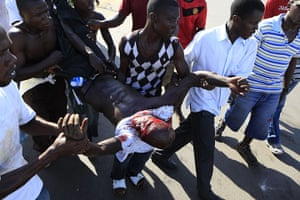 Liberia violence: Opposition party supporters carry a wounded man during clashes
