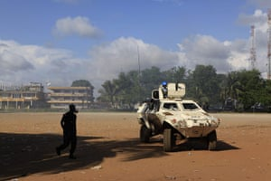 Liberia violence: A Liberian policeman in a gas mask walks past a UN armoured vehicle